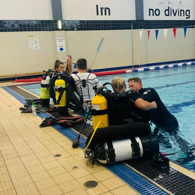 Maddie and Kristine from Northern Diver at a Chorley BSAC Try-Dive session - checking regs and the equipment fit