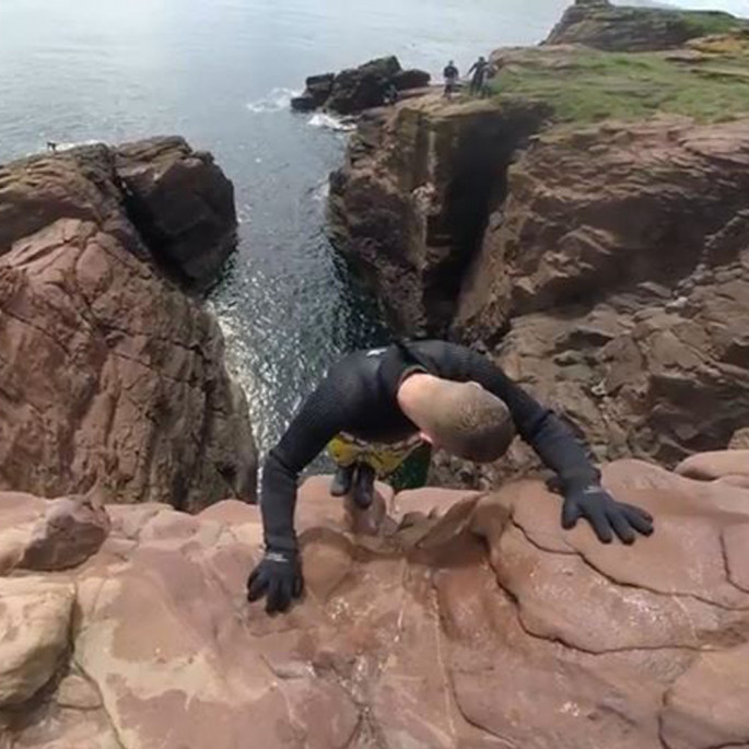 Chris Murphy on a cliff face preparing to cliff jump in his Northern Diver gloves and wetsuit
